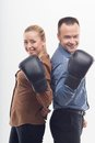 Coworkers in boxing gloves young attractive business women and men with standing back to back isolated on white background Royalty Free Stock Photography