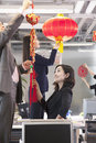 Coworkers hanging decorations in office for chinese new year Royalty Free Stock Photos