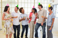 Coworkers laugh and celebrate accomplishment and enjoy party in the office Stock Photography