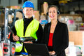 Coworkers at warehouse of forwarding company teamwork warehouseman or forklift driver and female supervisor with laptop headset Stock Images