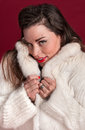 Coy pinup girl in fur coat against red background Stock Photos