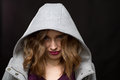 Coy or shy young woman wearing a hood peering out at the camera with her head down against dark background Royalty Free Stock Images