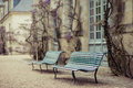 Cozy benches bench near the old building where the tree grows Royalty Free Stock Photo