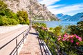 Cozy city street of Limone Sul Garda with paving stone sidewalk, blooming flowers on a metal railings, growing trees with amazing Royalty Free Stock Photo