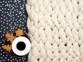 Cozy composition, closeup merino wool blanket, warm and comfortable atmosphere. Knit background. Cup of coffee and ginger cookies.