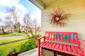 Cozy decorated porch with painted red bench and dry branch on th yellow wicker baskets overlooking the front view Royalty Free Stock Image