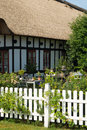 Cozy garden in front of old half timbered house with thatched roof Stock Photos