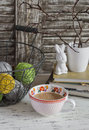 Cozy home seat with a basket with yarn, stacked books, vase with dry branches,a ceramic rabbit and a Cup of tea with milk. Royalty Free Stock Photo