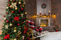 Cozy living room with rocking chair, decorated modern flaming fireplace and large Christmas tree with a lot of presents Royalty Free Stock Photo