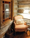 Cozy Chair in a Log Cabin Corner Royalty Free Stock Photo