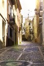 The cozy street of the old European city of Relleu is paved with cobblestones in the form of a picture. Mediterranean architecture Royalty Free Stock Photo