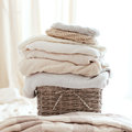 Cozy sweaters stack of knitted in wicker backet Royalty Free Stock Image