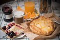 A cozy sweet breakfast in bright colors. Apple pie with cherry jam and cups of hot coffee and fresh orange juice. Royalty Free Stock Photo