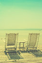 Cozy white beach chair facing seascape with vintage filtered image Royalty Free Stock Images