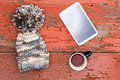 Cozy winter cap tablet and tea on a grungy table woolly with large decorative pompom lying with computer mug of fresh wooden with Royalty Free Stock Photo
