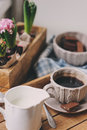 Cozy winter or spring morning at home coffee milk and chocolate on wooden tray hyacinth flowers on background warm mood selective Stock Photo