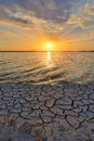 Cracked earth on seacoast sunset background Stock Images
