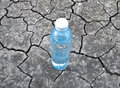 Cracked ground with water in a bottle Stock Photo