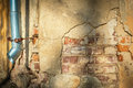 Cracked house wall with hanging metal drainpipe yellow of old building visible red bricks few layers of materials downspout Royalty Free Stock Photography
