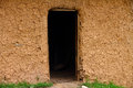 Cracked mud house wall with dark doorway a exterior a darkened Royalty Free Stock Photography