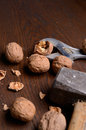 Cracking nuts with heavy tools on a wooden table Royalty Free Stock Image