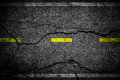 Cracks on asphalt the yellow line dividing lanes to illustrate a general background Stock Photo