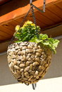 Craft flower pot made of woven wicker suspended with chains Royalty Free Stock Photos