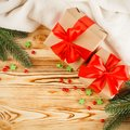 Craft gift boxes with red ribbon and bow, green Christmas tree, decorations, white plaid on wooden background. Xmas and New Year c Royalty Free Stock Photo