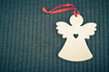 Craft wooden angel on grey knitted background love symbol Stock Photos
