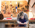 Craftsman in his workshop leveling the frets of a guitar Royalty Free Stock Photo