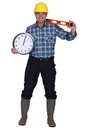 Craftsman holding a clock and level Royalty Free Stock Photography