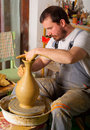 Craftsman making vase from fresh wet clay Stock Image