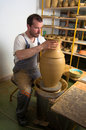 Craftsman making vase from wet clay on pottery whe Stock Image