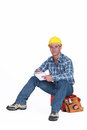 Craftsman with notebook sitting on toolbox Royalty Free Stock Photos