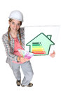 Craftswoman holding energy consumption label Royalty Free Stock Image