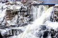 Craggy waterfall on a freezing cold day with ice hanging from rocks Stock Photo