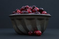 Cranberries in metal bowl with berries out of bowl fresh red and maroon heaped above silvered colored vintage or food mold three Royalty Free Stock Images