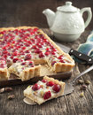 Cranberry and pistachio tart with white chocolate cream on wooden table Stock Photos