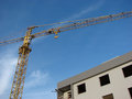 Crane and building mechanical next to apartment in a blue sky day Stock Photo