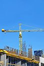 Crane and construction site building against blue sky Royalty Free Stock Images