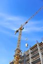 Crane and construction site building against blue sky Stock Image