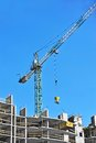 Crane and construction site building against blue sky Stock Photo