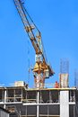 Crane and construction site building against blue sky Stock Images