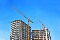 Crane and construction site building against blue sky Stock Photos