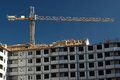 Crane at construction site front view of tall on modern blue sky Royalty Free Stock Photo