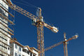 Crane at construction site front view of tall on modern blue sky Stock Photo