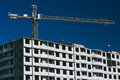 Crane at construction site front view of tall on modern blue sky and small people in the windows Royalty Free Stock Image