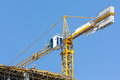 Crane on construction site over blue sky scaffolds Royalty Free Stock Images