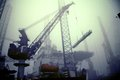 Crane in a harbor working at the of ijmuiden the netherlands on foggy day Royalty Free Stock Photos