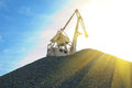 Crane at heap of gravel on blue sky background Stock Photos
